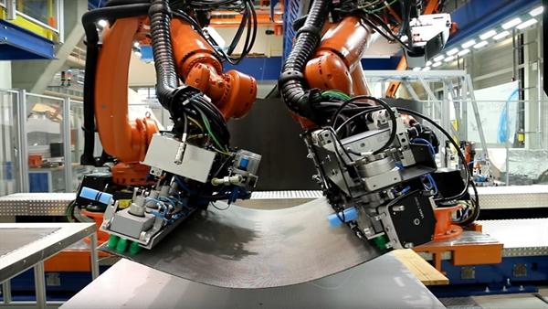 Zwei kollaborierende Roboter beim Transport eines CFK%2dZuschnitts