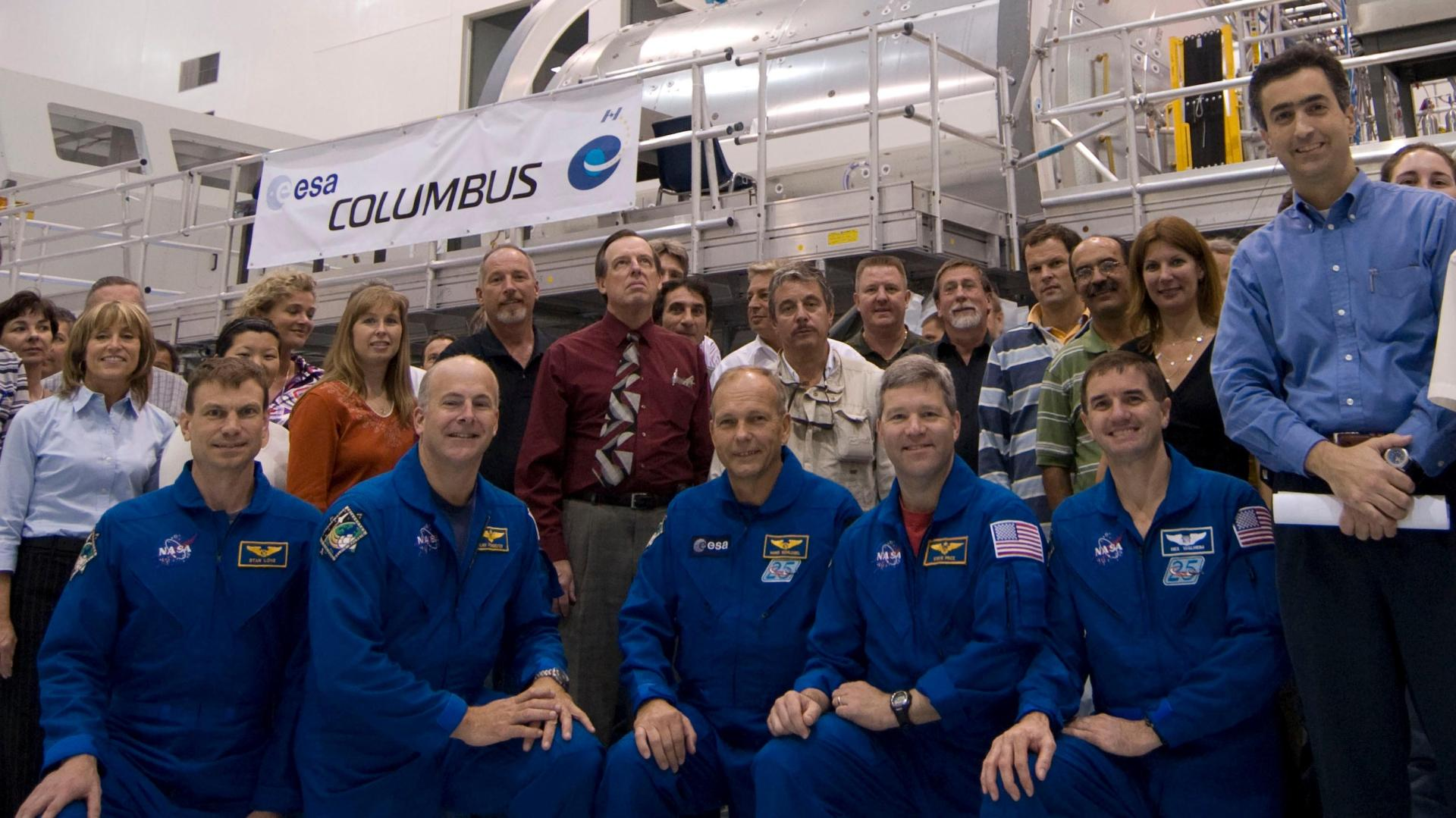 STS-122 astronauts (kneeling) and support team with the European Columbus laboratory