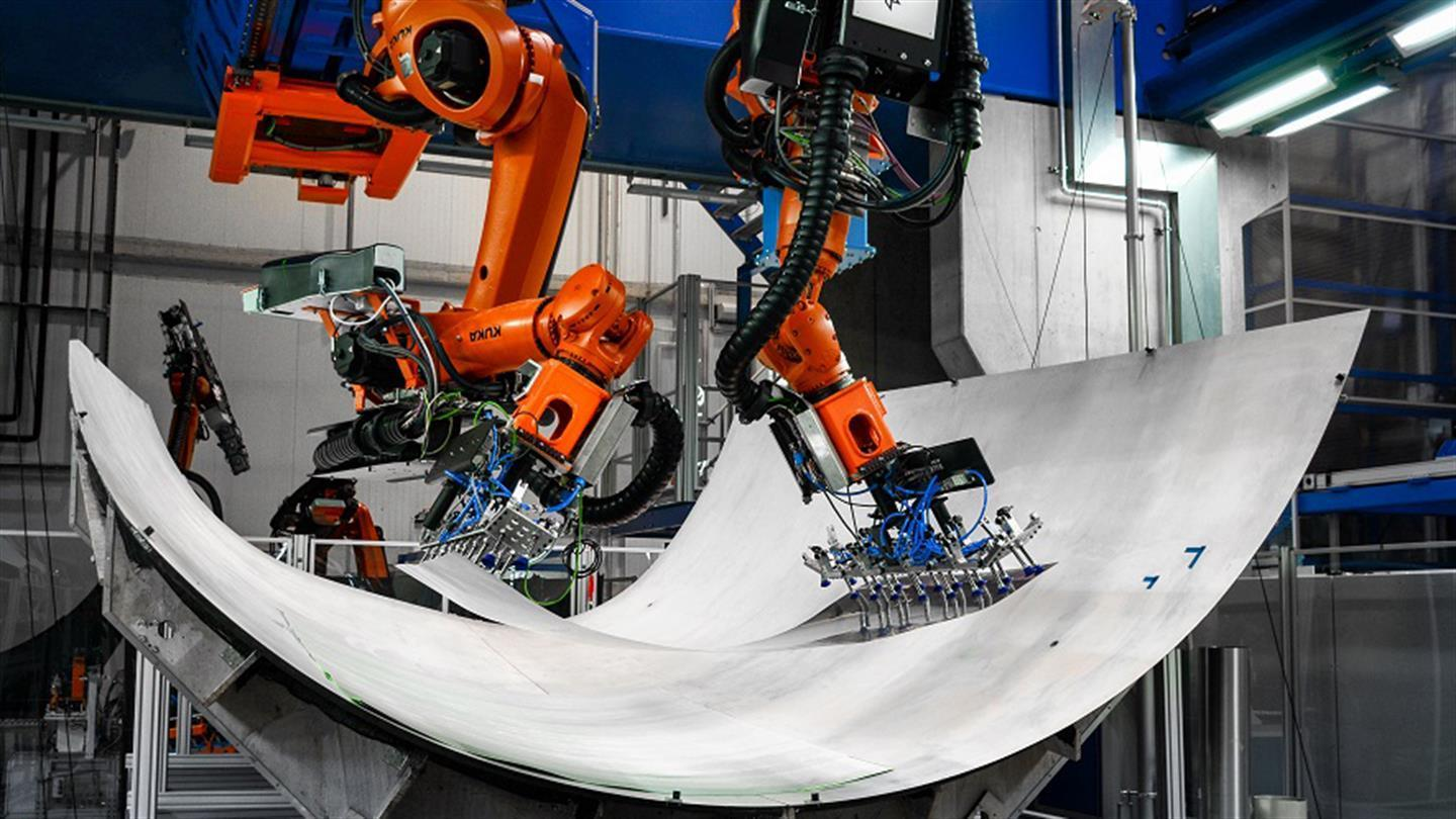 Two Robots lay aluminium sheets