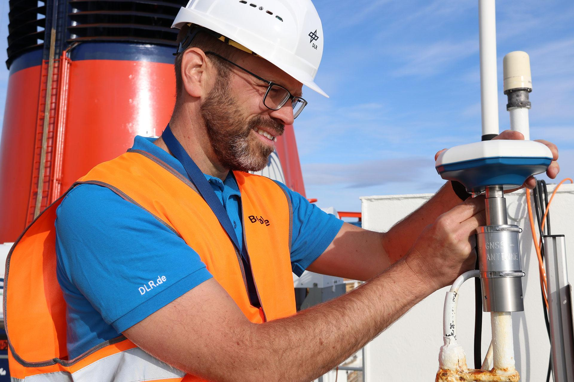 DLR project leader Simon Plass attaches a receiving antenna to Polarstern's upper deck