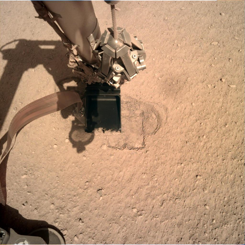The robotic arm of the InSight lander at the Mole hole
