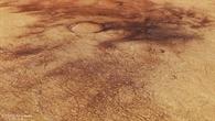 Perspektivischer Blick auf Staubteufelspuren in Chalcoporos Rupes