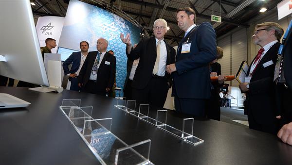 Prof. Hansjörg Dittus, DLR%2dVorstand für Raumfahrtforschung, erklärt Olaf Lies, dem Wirtschaftsminister des Landes Niedersachsen, das Exponat Plate Lines