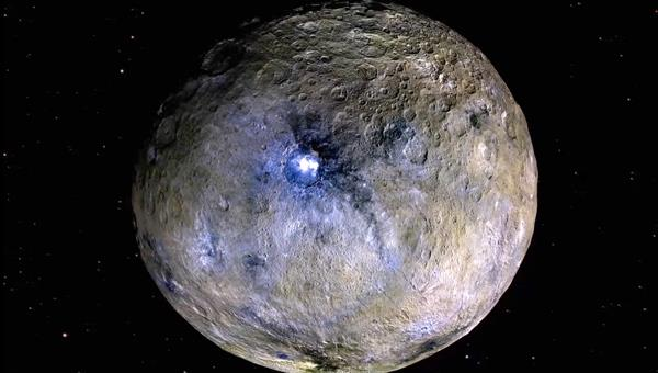 At the centre of the 90 kilometre%2dwide impact structure Occator is the largest occurrence of the strange white deposits on Ceres. These are principally carbonates, salts and carbonic acid. The blue false colours also indicate the existence of bright deposits associated with sulphuric salts, popularly known as plaster. Credit: NASA/JPL%2dCaltech/UCLA/MPS/DLR/IDA