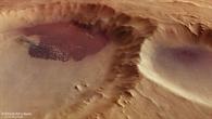 Blick in einen Krater mit dunklen Dünen in der Region Aonia Terra