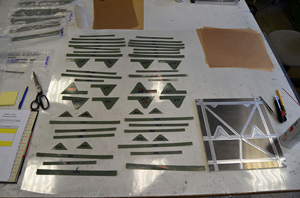 Figure 4: Machine%2dcut semi%2dfinished parts made of CFRP fibre composite plastic (prepreg) for making the surface layers for one of the side walls of the MASCOT lander. At the bottom right is the mould in which the Individual cut parts are laid and then glued orcured.<br />Credit: DLR (CC%2dBY 3.0).