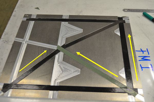 Figure 5: Mould for producing the surface layers for one of the side walls of the MASCOT lander, with the prepreg semi%2dfinished components already installed. The yellow arrows indicate the orientation of the fibres in the prepregs along the framework struts.<br />Credit: DLR (CC%2dBY 3.0).