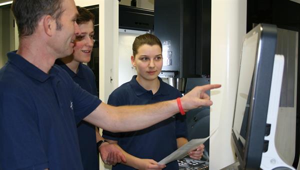 Auszubildende bei Einweisung an CNC gesteuerter Fertigungsmaschine