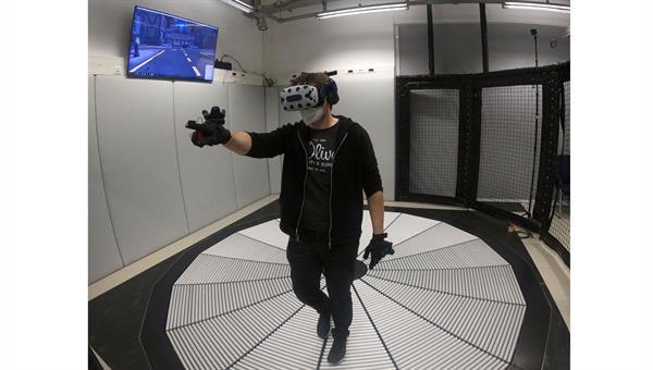 Ein DLR%2dWissenschaftler beim Durchführen einer VR%2dStudie im Fußgängersimulator