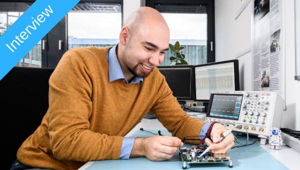 Jan Sommer mit einem Entwicklungsboard an seinem Arbeitsplatz