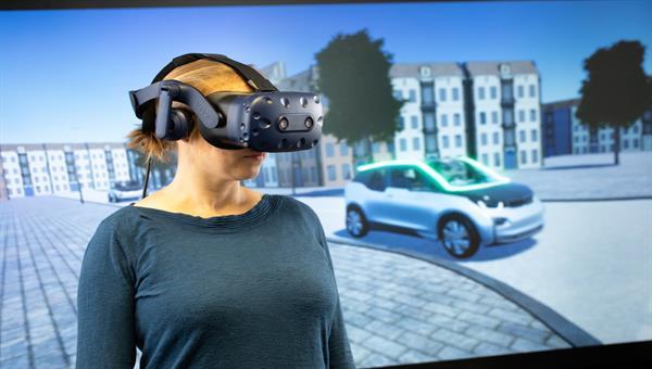 Versuchsteilnehmerin interagiert mit einem automatisierten Fahrzeug in der VR