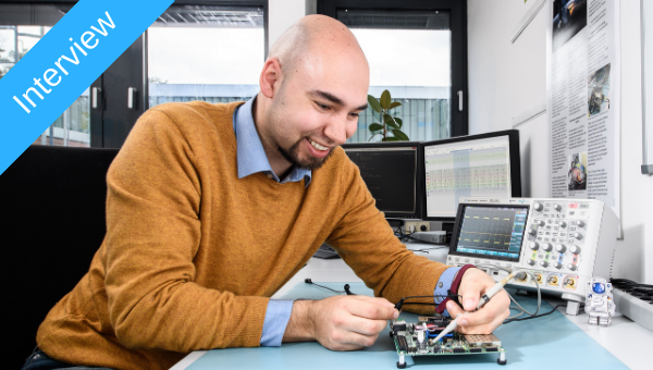 Jan Sommer at his desk with a development board