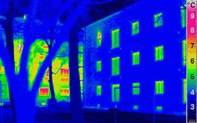 """Wärmebild von Häusern. Links im Hintergrund ein normales Haus, das recht viel Wärme abgibt. Rechts ein gut isoliertes """"Passivhaus"""", das viel weniger Energie verbraucht. Bild: Passivhaus Institut"""