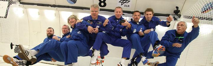 Hui! Schlagartig setzt bei Parabelflügen Schwerelosigkeit ein. Hier einige der Lehrerinnen und Lehrer – zusammen mit dem deutschen ESA-Astronauten Reinhold Ewald (Vierter von links in der Bildmitte). Bild: DLR, Jörg Adam