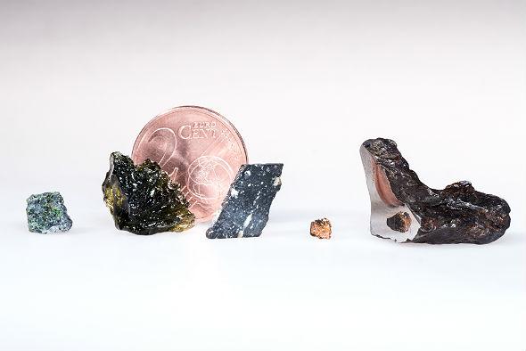 Diese Bruchstücke von außerirdischer und irdischer Materie sind in der Kapsel. Von links nach rechts: Ein Stück des geheimnisvollen Meteoriten NWA 7325, der vielleicht vom Merkur stammt, ein Stück Moldavit, eine dünne Scheibe Mondgestein, ein kleines Steinchen vom Mars und ein Stück eines Asteroiden, das nachträglich aufgeschnitten und poliert wurde, sodass die Schnittfläche spiegelblank ist.