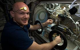 Alex mit einem Temperatur-Sensor. Gleichzeitig ist er an der Handschuhbox mit einem Experiment zur Verbrennungsforschung beteiligt. Bild: NASA, ESA
