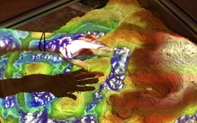 In der virtuellen Sandbox kann man eine Landschaft aus echtem Sand modellieren – und darauf wird dann per Rechner in Echtzeit ein farbiges Höhenmodell projiziert. Bild: DLR