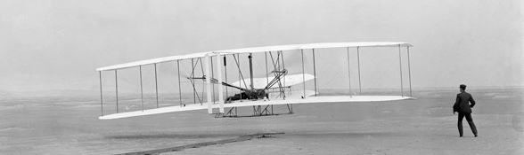 Die Gebrüder Wright bei einem Flugversuch. Sie gehörten zu den großen Luftfahrt-Pionieren. Bild: John T. Daniels, Library of Congress