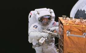 Weltraumspaziergänge sind harte Arbeit: Hier repariert Claude Nicollier aus der Schweiz einen Satelliten. Bild: ESA, NASA
