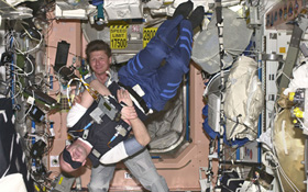 Gennady Padalka aus Russland (im Hintergrund) hilft ESA-Astronaut André Kuipers aus den Niederlanden bei einem medizinischen Versuch. Es geht dabei um den Gleichgewichtssinn. Bild: ESA