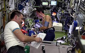 Alexander Kaleri aus Russland (links) und ESA-Astronaut Pedro Duque aus Spanien führen ein medizinisches Experiment durch. Wie man sieht, ist die ISS mit wissenschaftlichen Geräten geradezu vollgestopft: ein fliegendes High-Tech-Labor. Bild: ESA