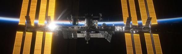 Auf diesem Bild sieht man die ISS vor der Nachtseite der Erde. Die aufgehende Sonne beleuchtet das dünne Band der Atmosphäre. Bild: NASA