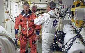 Wenige Stunden vor dem Start: Thomas Reiter wird von Technikern zur Einstiegsluke der Raumfähre begleitet. Bild: NASA