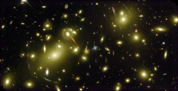 Hier sehen wir das kurvenförmig verzerrte Licht weit entfernter Galaxien. Es wird auf dem Weg zu uns durch näher gelegene Sternenhaufen abgelenkt. Dieser sogenannte Gravitationslinsen-Effekt zeigt also die Krümmung des Raumes durch große Massekonzentrationen. Bild: NASA, ESA, Hubble