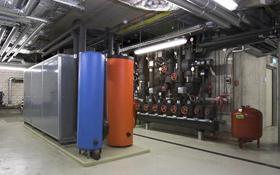 So sieht eine Wärmepumpe aus. Das kalte Wasser wird im blauen Behälter gespeichert, das warme Wasser im roten Tank. Bild: BMU (B. Hiss)