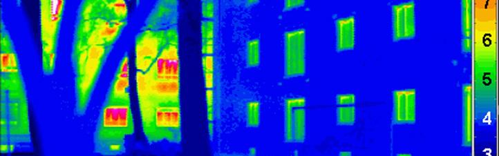 """Mit einer speziellen Kamera wurde dieses """"Wärmebild"""" gemacht. Links ist im Hintergrund – teils von einem Baum verdeckt – ein normales Haus zu erkennen. Die roten und grünen Stellen zeigen an, wo Energie verschwendet wird. Rechts ist ein Passivhaus zu sehen – hier sind die Wände sehr gut isoliert, was man an der blauen Farbe sieht. Bild: Passivhaus Institut"""