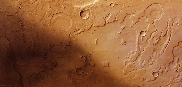 Dieses Bild der vom DLR entwickelten Kamera HRSC zeigt das Tiefland Acidalia Planitia auf der Nordhalbkugel des Mars. Man erkennt auch ausgetrocknete Flusstäler, die belegen: Hier muss früher einmal Wasser geflossen sein. In dieser Gegend beginnt die Geschichte von Mark Watney, der im Film von Matt Damon gespielt wird – mehr wird nicht verraten! Bild: ESA, DLR, FU Berlin