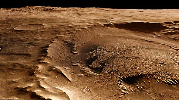 Nochmal der kleine Krater am Rand des riesigen Schiaparelli-Kraters – hier aber so, als ob man ihn im Tiefflug fotografiert hätte. Doch der Schein trügt: Auch dieses Bild stammt von der deutschen HRSC-Kamera aus mehreren hundert Kilometern Höhe. Wie das? Die Daten dieser Stereokamera lassen sich per Bildverarbeitung eben auch in solche perspektivischen Ansichten umwandeln.