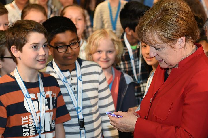 Im Schülerlabor bekommt Merkel einen der legendären DLR-Leuchtkulis überreicht. Bild: DLR