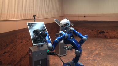 Robot Justin cleans the solar panels in the Martian landscape. Astronaut Scott Tingle sends commands from the ISS.