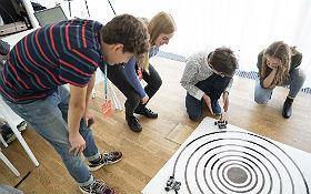 Die Workshop-Teilnehmer programmierten ihren ASURO-Roboter so, dass er vollkommen selbständig ein Ziel finden konnte. Auf diese Weise konnten sie sehr spielerisch nachvollziehen, wie komplex aber auch wie überaus spannend die autonome Robotersteuerung ist. Bild: © familie redlich AG