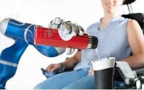 Der Assistenzroboter EDAN füllt, vom Rollstuhl aus gesteuert, einen Trinkbecher. Bild: DLR