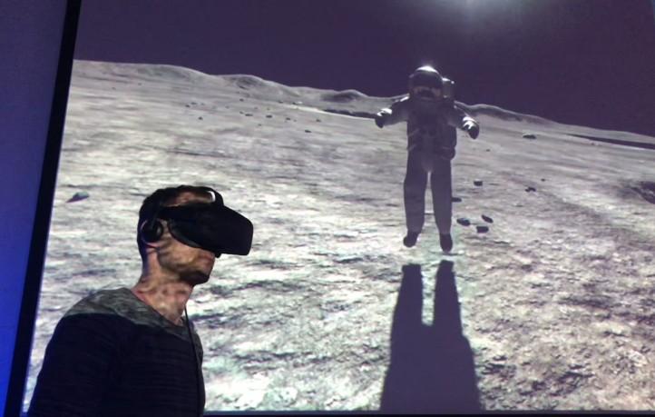 Tobias Bohnhardt führt das Publikum durchs Weltall. Hier ist er mithilfe einer VR-Brille zusammen mit Neil Armstrong auf dem Mond. Bild: DLR