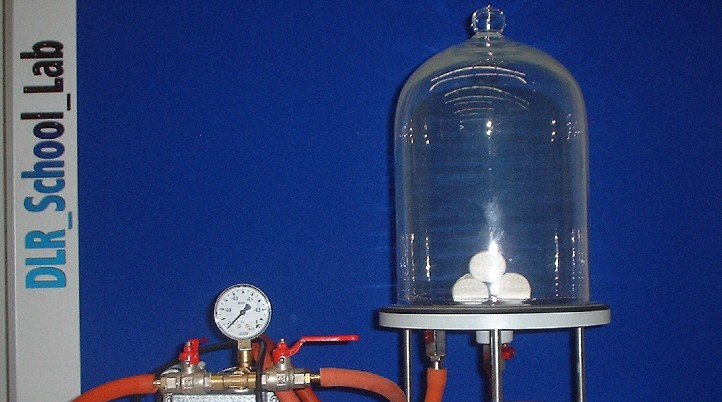 A vacuum pump and a bell jar. In front are the evacuated Magdeburg hemispheres. Credit: DLR (CC-BY 3.0)